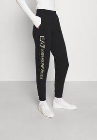 EA7 Emporio Armani - Pantalones deportivos - black/light gold - 0
