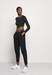 Calvin Klein Performance - Tracksuit bottoms - black - 1