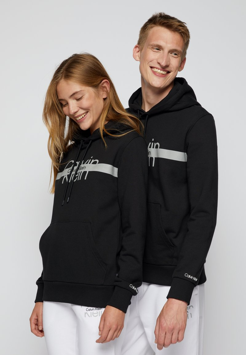 Calvin Klein - REFLECTIVE CHEST STRIPE HOODIE UNISEX - Sweatshirt - black