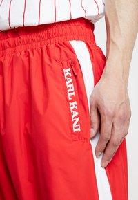 Karl Kani - RETRO TRACKPANTS - Tracksuit bottoms - red/white/black - 4