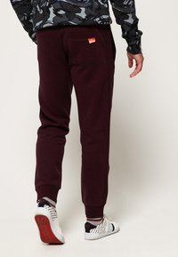 Superdry - LABEL CUFFED JOGGER - Tracksuit bottoms - bordeaux - 2