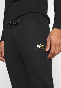 Alpha Industries - BASIC JOGGER FOIL - Tracksuit bottoms - black/yellow gold - 4