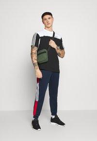 adidas Originals - CLASSICS  - Tracksuit bottoms - conavy/scarle - 1