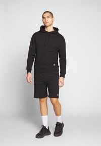 Russell Athletic Eagle R - FORESTER - Tracksuit bottoms - black - 1