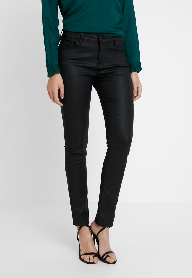 CADOU COATED - Trousers - black