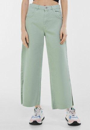MIT SCHLITZEN AM SAUM - Flared Jeans - khaki