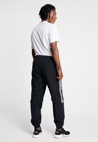 adidas Originals - LOCK UP - Tracksuit bottoms - black