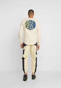 Nike Sportswear - RE-ISSUE - Pantalon de survêtement - black/team gold - 2