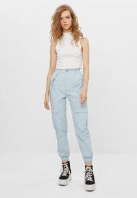 Bershka - MIT KETTE - Trousers - light blue - 1