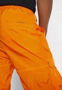 Karl Kani - SIGNATURE CRINCLE PANTS UNISEX - Pantalon cargo - orange - 4