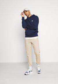 adidas Originals - ESSENTIAL HOODY UNISEX - Jersey con capucha - conavy - 1