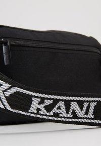Karl Kani - KK SIGNATURE TAPE HIP BAG - Marsupio - black/white - 2