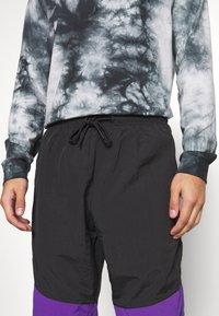 Urban Classics - CRINKLE TRACK PANTS - Tracksuit bottoms - black/ultraviolet/aqua - 4