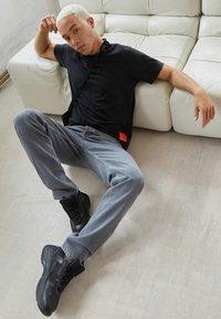 Calvin Klein Jeans - RELAXED BADGE TEE UNISEX - Print T-shirt - black - 1