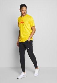 Nike Performance - DRY TEE TRAIL - Camiseta estampada - speed yellow - 1