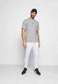 Nike Sportswear - REPEAT PRINT - Pantaloni sportivi - white/black - 1