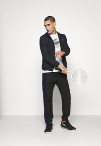Lacoste Sport - TENNIS PANT - Tracksuit bottoms - black/cosmic white - 1