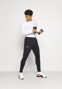 Under Armour - STORM PANTS - Tracksuit bottoms - black - 1