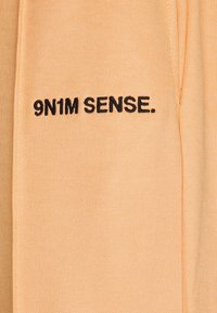 9N1M SENSE - LOGO PANTS UNISEX - Tracksuit bottoms - apricot/black - 6