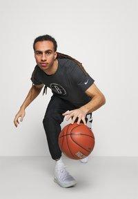 Nike Performance - STARTING PANT - Tracksuit bottoms - black/white - 3