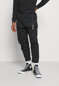 Converse - PANELED JOGGER - Cargo trousers - black - 0