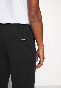 Lacoste LIVE - Tracksuit bottoms - black