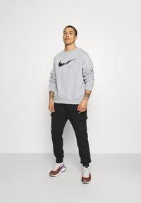 Nike Sportswear - ZIGZAG CARGO PANT - Verryttelyhousut - black - 1