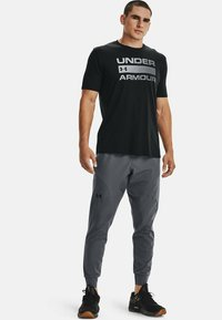 Under Armour - UA FLEX WOVEN JOGGERS - Tracksuit bottoms - grey - 1
