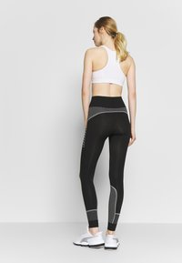 Puma - EVOSTRIPE EVOKNIT LEGGINGS - Tights - black - 2