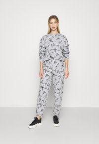 NEW girl ORDER - ACID BUTTERFLY JOGGER - Tracksuit bottoms - grey - 1