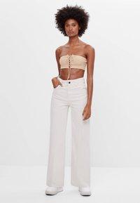 Bershka - MIT WEITEM BEIN - Flared jeans - beige - 1