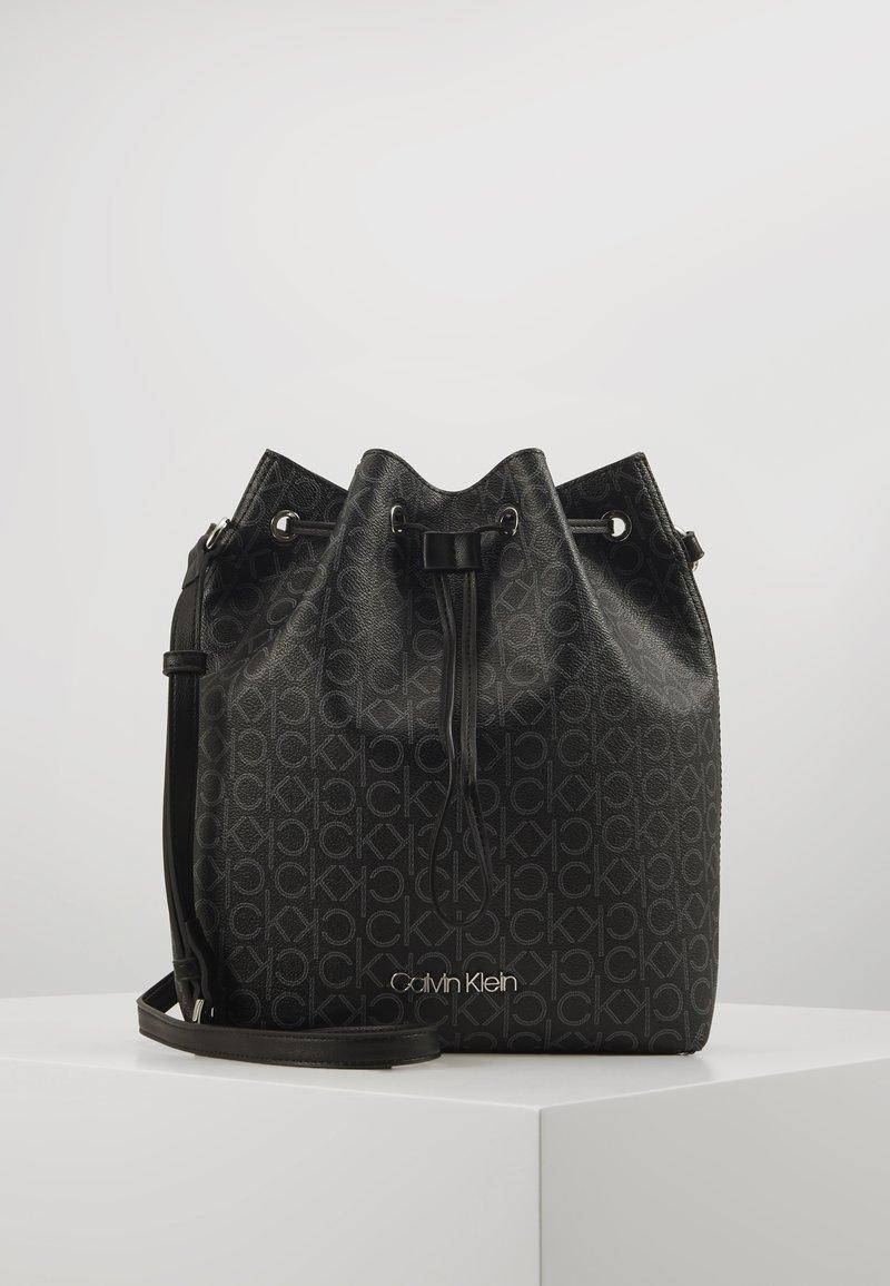 Calvin Klein - DRAWSTRING BUCKET BAG MONOGRAM - Sac bandoulière - black