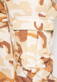Karl Kani - SIGNATURE CAMO CRINCLE PANTS - Cargo trousers - beige/sand - 3