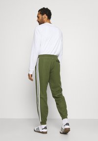 adidas Originals - UNISEX - Tracksuit bottoms - wild pine - 2