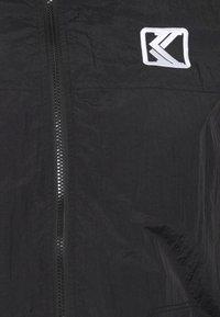 Karl Kani - SIGNATURE TRACKJACKET UNISEX - Summer jacket - black - 6