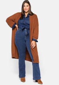 Sheego - Bootcut jeans - blue denim - 1