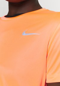 Nike Performance - MILER - T-shirt med print - bright mango/silver - 4