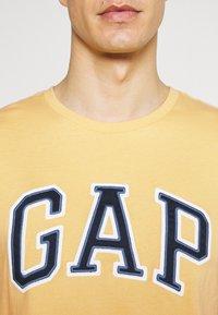 GAP - BAS ARCH - Print T-shirt - gold wash - 4