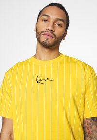 Karl Kani - SMALL SIGNATURE PINSTRIPE TEE UNISEX - Print T-shirt - yellow/white - 4