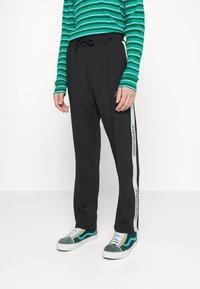 Pegador - WIDE TRACKPANTS UNISEX - Pantalon de survêtement - black/mint - 0