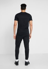 Nike Performance - Tracksuit bottoms - black/white - 2