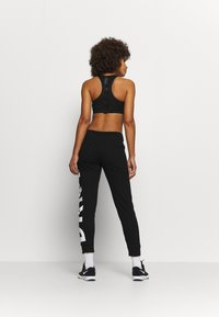 DKNY - EXPLODED LOGO CUFFED - Tracksuit bottoms - black - 2