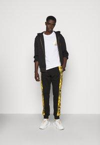 Versace Jeans Couture - PRINT LOGO BAROQUE - Teplákové kalhoty - black - 1