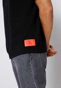 Calvin Klein Jeans - RELAXED BADGE TEE UNISEX - Print T-shirt - black - 4