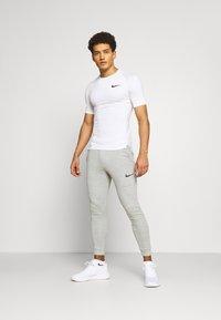 Nike Performance - PANT TAPER - Tracksuit bottoms - dark grey heather/black - 1