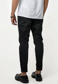 Tigha - Trousers - black - 2