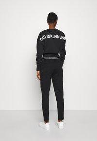 Calvin Klein Jeans - LOGO ELASTIC MILANO TROUSER - Trousers - ck black - 2