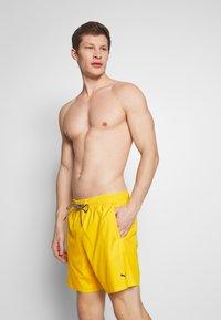 Puma - SWIM MEN MEDIUM LENGTH - Swimming shorts - yellow - 0
