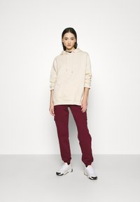Nike Sportswear - CARGO PANT LOOSE - Tracksuit bottoms - dark beetroot - 1
