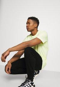 adidas Originals - COLLEGIATE CREST UNISEX - Tracksuit bottoms - black - 4